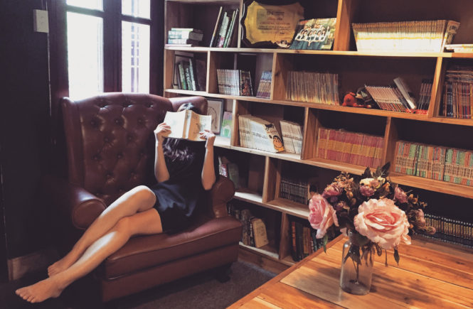 Canva - Woman Reading Book in the Library